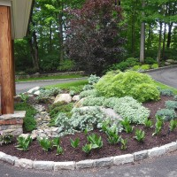 Simple foliage color and texture create this pleasing driveway planting bed in New Canaan.  Notice the use of boulders and natural river stone which provide additional textural interest.