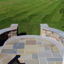 "This sitting wall was designed for a client in Katonah, NY. The circular motif of the sitting walls and the bluestone terrace were designed to tie into the lines of the residence. The sitting wall is constructed of fieldstone and topped with a 2"" rock-faced, bluestone cap. Note the decorative bluestone outline of the terrace, which accentuates the curved line of the walls."