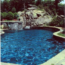 This spectacular kidney shaped pool in South Salem was designed to nestle into the rocky terrain. The natural setting dictated the natural shape of the pool and the native stone construction materials. The coping is constructed of irregular shaped grey granite. Note the use of the plant materials to soften the stone edges and whimsical sculpture to enhance the experience.