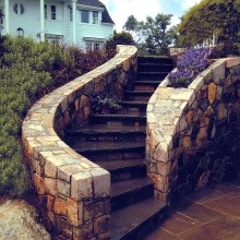 The undulating line of this set of stairs beckons the visitor to climb to the next level at this home in Westport, CT. Constructed of fieldstone with bluestone treads, the stairs wind upwards from the patio to the upper garden. Note the built-in planter in the stair wall.