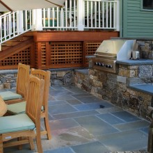 The sophisticated and clean lines of this outdoor terrace and built-in grill were a collaboration with our client in Katonah, NY. The fieldstone walls and rock-face bluestone coping are attractive and functional. The random pattern bluestone terrace ties in beautifully with the coping and walls.