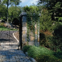 """This custom designed front entry was constructed for a client in South Salem, NY. The fieldstone columns are topped with massive 4"""" bluestone caps and softened with elegant planters filled with cascading flowers and foliage. The distinctive black wrought iron gates were custom designed in concert with the client."""
