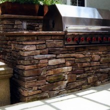 "This custom-designed outdoor built-in grill was constructed for a client in Westport, CT using earth-tone fieldstone for the walls and matching 2"", rock-face, fieldstone coping. Counters on either side of the grill allow for food prep. Note the electrical outlet for appliance use."