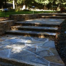 Wide and inviting, these entry steps at a home in North Stamford, CT, provide a functional, safe and attractive path. Note the flared entry to the steps that leads into the fieldstone risers and treads of the steps. Path lights illuminate the area at night for an additional element of safety.