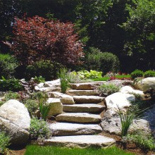 In New Canaan, the addition of a poolhouse in the backyard of this property created some grade changes. Access from one area of the backyard to another was facilitated beautifully by these lovely boulder and stone steps. Note the lush and colorful plantings which enhance the journey.