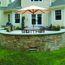In Redding, CT, this spacious patio was built for outdoor entertaining and family gatherings. Note the rockface bluestone cap to the sitting wall constructed of brown fieldstone.