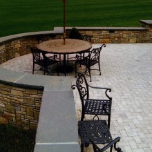 "This sitting wall and terrace were designed and constructed for a client in Redding, CT. The fieldstone sitting wall was built in a Asher-Bond pattern. The 2"" thick bluestone coping with rock-face that tops the sitting wall gives the area a sophisticated and finished look. Light grey pavers were utilized as the patio surface."
