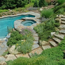 In North Stamford, an extremely steeply sloped backyard was a challenging spot to add a pool. Access from the main house to the natural shaped pool at the edge of the woodland, called for our boulder and stone slab steps. The long journey to and from the pool is eased by the flights of steps and the lovely plantings.