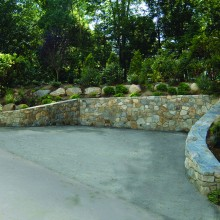 At this residence in New Canaan, CT, the homeowner was desperate for additional parking. The property was significantly sloped which made the site especially challenging. We were able to add two additional parking spaces by carving out and building a fieldstone retaining wall along the existing driveway.