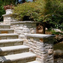 Chiseled rockface edges on the bluestone treads and bluestone caps, add a distinguished and elegant feel to these entry steps in New Canaan, CT.