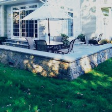 This cottage in Greenwich, CT includes this charming patio with fieldstone sitting wall capped with rodeface chiseled bluestone.