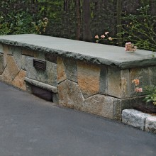 This driveway bridge in Old Greenwich, CT was constructed with low fieldstone side walls, capped by rockface bluestone. Weep holes at the base of the wall allow water to drain efficiently to the stream below.