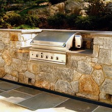 """On a steeply graded site in Chappaqua, NY, we designed and built a cozy bluestone terrace with 4"""" patio drains and a 36"""" stainless steel grill nestled into the hillside retaining walls."""