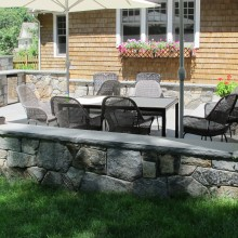 "In Westport, CT, we designed and built this spacious outdoor bluestone terrace surrounded by a fieldstone sitting wall. Note the 2"", rock-face, bluestone coping which makes for comfortable seating for casual get-togethers. The terrace also features a large 48"" built-in grill with storage cabinet and an outdoor stainless-steel refrigerator."