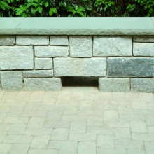 This grey stone terrace, in Redding, CT, is flanked by a fieldstone sitting wall with a rock face bluestone cap. The large weep hole at the base allows water to drain off with ease.