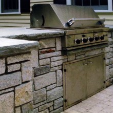 "For this client in Greenwich, CT, we designed and constructed a built-in grill and storage unit utilizing pale grey granite with counters of 2"", rock-face bluestone."
