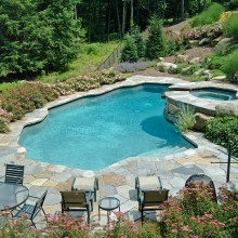 In North Stamford, in collaboration with the pool company, we constructed this natural shaped pool at the base of an extremely steeply sloped backyard. The pool fits nicely at the edge of the woodland. The masonry work, coping, pool terrace and stone slab steps enhance the naturalistic feeling. Access from the main house to the natural shaped pool at the edge of the woodland, called for our boulder and stone slab steps. The long journey to and from the pool is eased by the flights of steps and the lovely plantings.