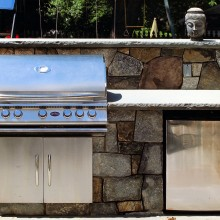 "In Westport, CT, we designed and built this outdoor kitchen area with a large 48"" grill with storage cabinet and an outdoor stainless-steel refrigerator."