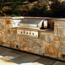 This built-in grill in Chappaqua, NY was set in a fieldstone retaining wall with weep holes at the base of the wall to allow for proper drainage from the steep hillside above it, and a 4