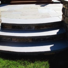 These circular bluestone steps were created for a client in Katonah, NY. Flanked by fieldstone walls with bluestone coping, the steps are an elegant transition from the terrace to the yard.